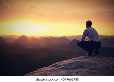 Hiker in black sit alone on the rock summit. Wonderful daybreak in mountains, heavy mist in deep valley. Man sit on the rock.