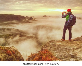 Hiker blogger taking photo by smartphone of fall sunset mountains landscape. Sharing travel lifestyle and adventure vacations. Use outdoor modern technology