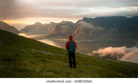 Hiker blogger taking photo by smartphone of fall sunset mountains landscape. Sharing travel lifestyle and adventure vacations. Lofoten islands, Norway