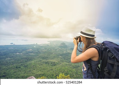 Hiker with camera and backpack taking picture of beautiful valley. Travel concept.