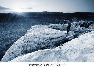 Hiker with camera on tripod takes picture from rocky summit. Alone photographer at edge photograph misty landscape colorful forest in valley.