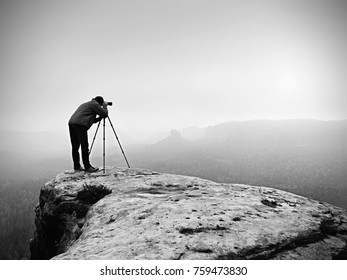 Hiker with camera on tripod takes picture from rocky summit. Alone photographer at edge photograph misty landscape, forest in valley.
