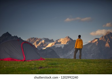 Hiker in a camp and looking at mountains in a sumer day.