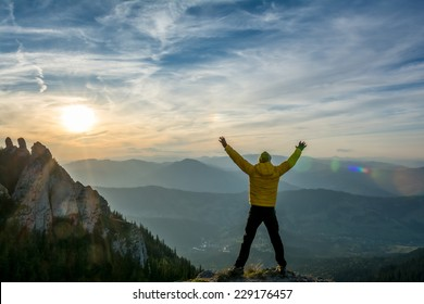 hiker celebrates success in the sunset above the valley
