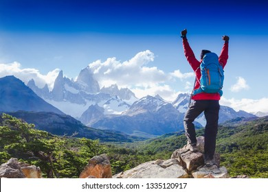 hiker celebrating success on top of a mountain in a majestic Patagonia mountain landscape. Fitz Roy, Argentina. Mountaineering sport lifestyle concept