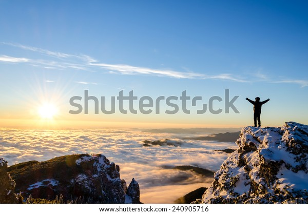 hiker celebrating success on top of a mountain in a majestic sunrise