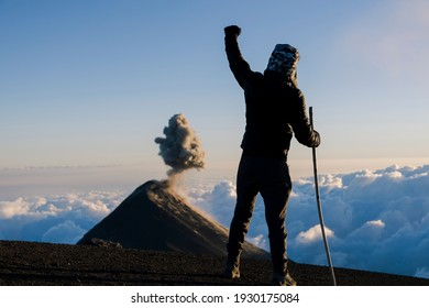 Hiker celebrating at the top of the Acatenango volcano watching the volcano of fireerupting - excited climber on top of the mountain watching an erupting volcano - volcanoes Guatemala