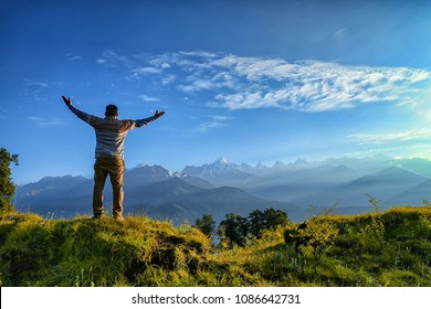 Hiker cheering elated and blissful with arms raised in the sky after hiking. Uttarakhand, India.