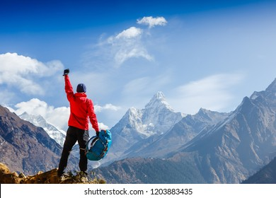 Hiker cheering elated and blissful with arms raised in the sky after hiking. Everest base camp trek