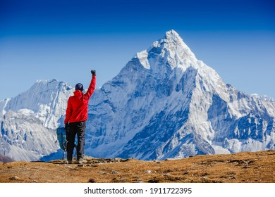 Hiker cheering elated and blissful with arms raised in the sky after hiking. Everest base camp trek. Ama Dablam mountain view. Himalayas, Nepal