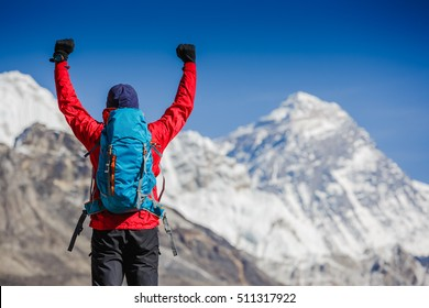 Hiker cheering elated and blissful with arms raised in the sky after hiking. Everest mountain on the backgroung - the world highest peak