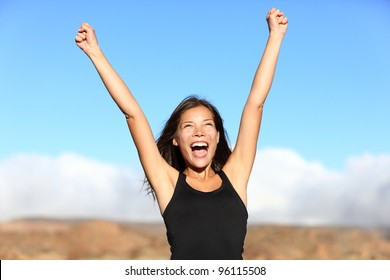 Hiker cheering. Woman hiking cheerful with arms stretched screaming of joy on top of mountain. Beautiful sporty mixed ethnicity woman outdoor.