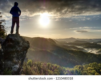 Hiker climbed on rock above foggy valley. Hrensko range, Czech Republic, 21st of Seprtember 2018.  Man watch over misty morning valley to bright morning Sun.