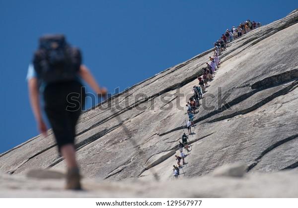 Hiker climbing on a rock, Half Dome, Yosemite Valley, Yosemite National Park, California, USA