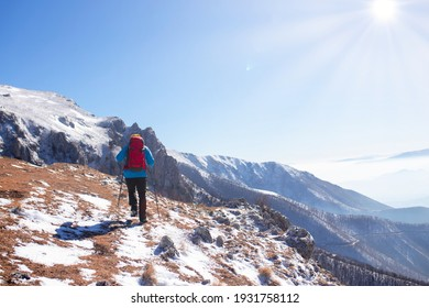 The hiker climbs to the top of the mountain covered in snow.