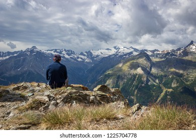 The hiker contemplates the view of Gran Paradiso group from a solitary place. Concept of solitude, meditation, astonishment and relax. Aosta valley, Italy. Self-portrait