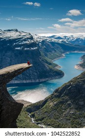 Hiker Couple sitting on a cliff over a lake, Trolltunga, Norway Concept of adventure, freedom and extreme lifestyle