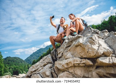 Hiker couple with small yellow dog sitting on mountain peak and  taking picture with smart phone