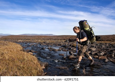 Hiker crosse the River with backpack