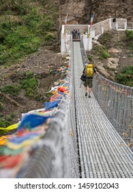 Hiker crossing a metal suspension bridge in Nepal, part of the trail to Annapurna Sanctuary.