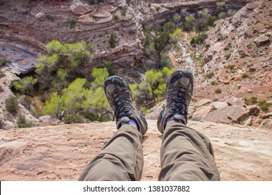 A hiker dangles his feet over the edge of a cliff looking down into a desert canyon in this first person pov photo.