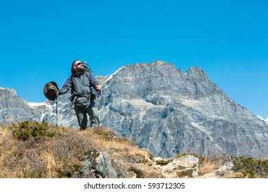 Hiker in dark grey Jacket and Pants staying on grassy Ridge relaxed and happy overlooking Mountain Scenery