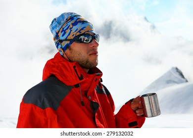 hiker drink coffee or tea in beautiful Himalaya mountains on hiking trip, Nepal. Active person resting outdoors in winter white nature