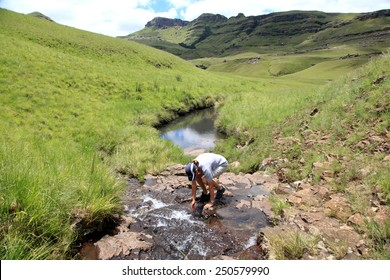 Hiker drinking fresh mountain water from a stream.