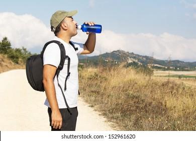 Hiker drinking water from bottle.
