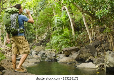 A hiker drinks some water next to a beautiful stream.