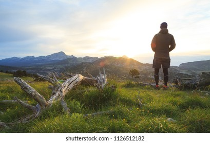 Hiker enjopying a tranquil sunrise in a mountain wilderness. Vercors, France.