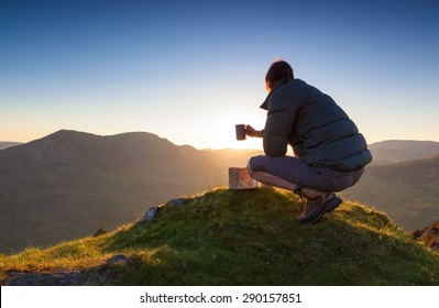 A hiker enjoying a hot drink at sunset on Fleetwith Pike. Lake District UK.