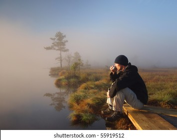 Hiker enjoying a morning coffee in a marsh by the lake