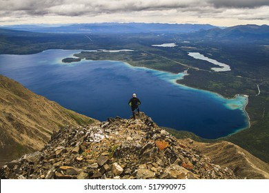 Hiker enjoying the view above the Kathleen lake during hike to King's Throne summit in Saint Elias Mountains in Kluane National Park, Yukon, Canada, North America.