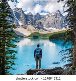 Hiker enjoying the view at Moraine Lake in Banff National Park, Canadian Rockies, Alberta, Canada.