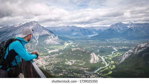 Hiker enjoying view on beautiful alpine valley with mountains and river flowing through it, shot at Sulphur Mountain Lookout, Banff National Park, Alberta, Canada