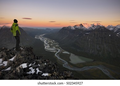 Hiker enjoying the view of a river carved valley, Rapadalen, Sweden