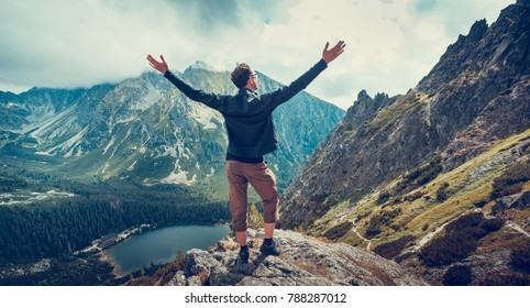 The hiker enjoys the magnificent serene view standing on the edge of the precipice in the Tatra Mountains in Slovakia. The Greeting to the sun. Majestic panoramic view. Relaxing and peacefulness.