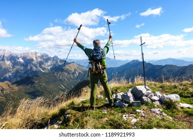 Hiker exults for having arrived on top of the mountain. Mature male.