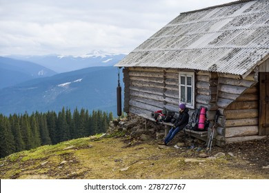 hiker female sitting outdoors near wooden house in the mountains