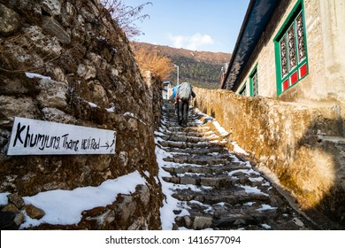 Hiker follow road sign on the way to the Everest Base Camp from Namche Bazaar