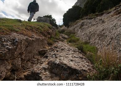 hiker following iberic road ruins