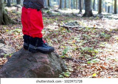 A hiker in the forest wearing a red gaiter.