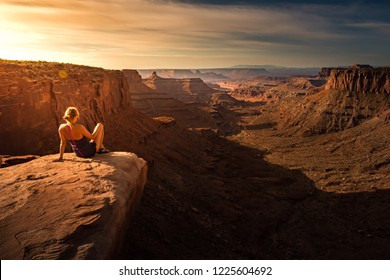 Hiker Girl admires Sunrise at East Fork Shafer Canyon near Dead Horse Point State Park Canyonlands Utah USA
