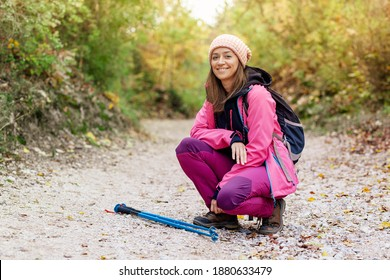 Hiker girl crouching on a wide trail in the mountains. Backpacker with pink jacket in a forest. Healthy fitness lifestyle outdoors.