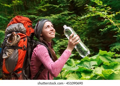 Hiker girl drinking water. Happy woman tourist with backpack in nature. Young female hiking with bottle
