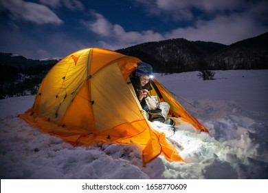 Hiker girl eating freeze dried food on a camping trip on a night mountain background. Joyful and healthy young girl in a tent enjoying hiking.Hiker living active lifestyle in mountain nature.