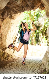 hiker girl jumping in a passage in rocks with stone pavement surface