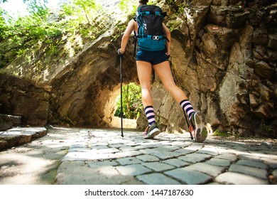 hiker girl walking through a passage in rocks with stone pavement surface