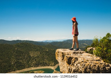 Hiker girl watching the beautiful view from the top of a cliff